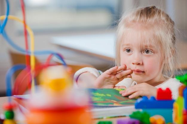 Linda criança em idade pré-escolar olhando para longe Foto gratuita