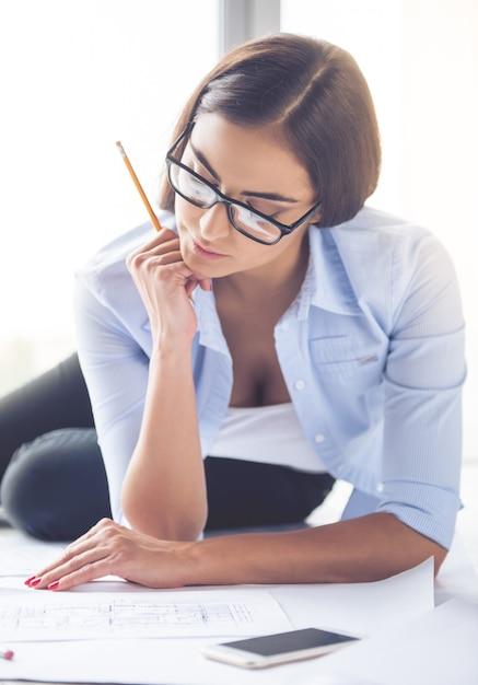 Linda designer feminina em óculos está segurando uma caneta. Foto Premium