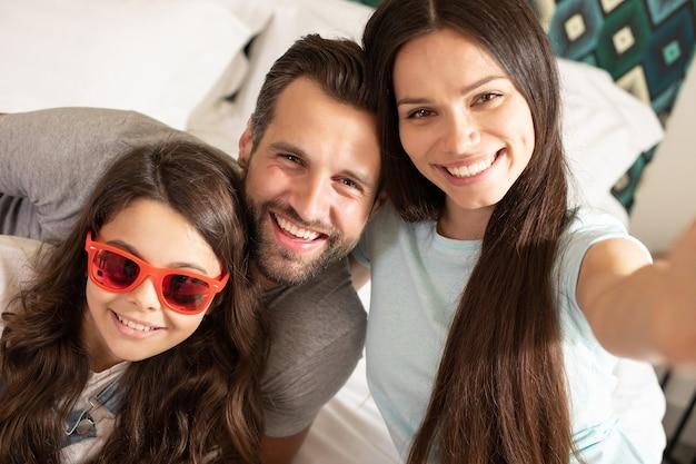 Linda e jovem família feliz tirando fotos de selfie no quarto e se divertindo juntos Foto Premium