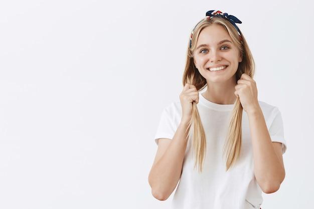 Linda elegante jovem loira posando contra a parede branca Foto gratuita