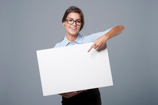 Linda empresária mostrando no quadro branco vazio Foto gratuita