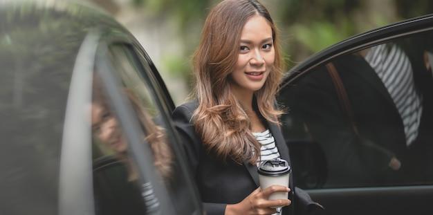 Linda empresária profissional saindo do carro moderno, segurando uma xícara de café Foto Premium