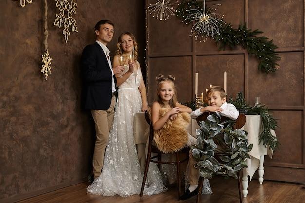 Linda família com dois filhos no quarto com decoração de natal Foto Premium