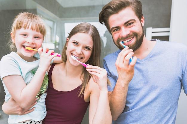 Linda família escovando os dentes para a câmera Foto gratuita