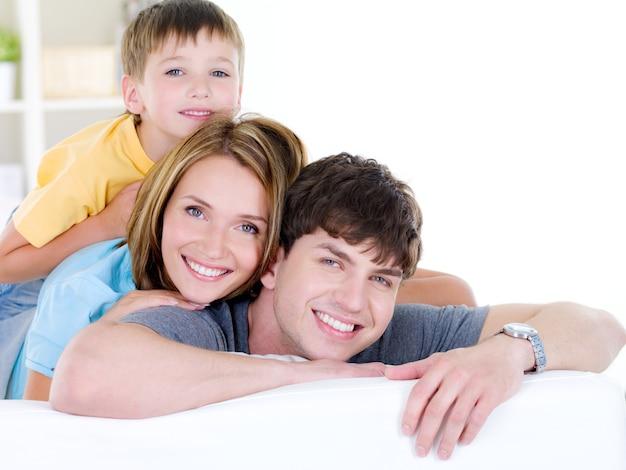 Linda família feliz e sorridente de três pessoas com filho pequeno - dentro de casa Foto gratuita