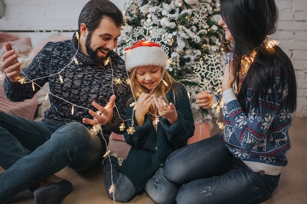 Linda família jovem aproveitando seu tempo de férias juntos, decorando a árvore de natal, organizando as luzes de natal e se divertindo Foto Premium