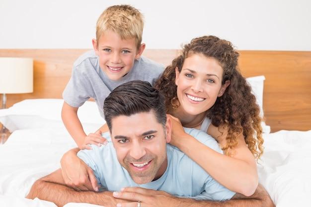 Linda família jovem sorrindo para a câmera na cama posando Foto Premium