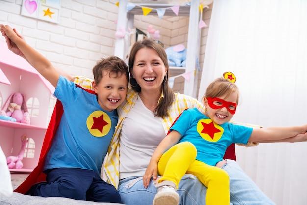 Linda família mãe e filha com o filho vestido com fantasias de super-heróis Foto Premium