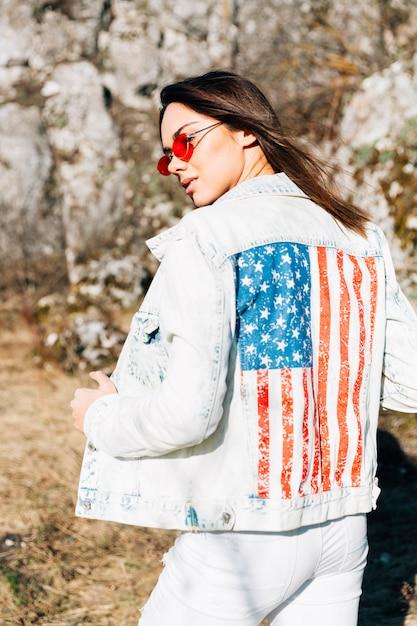 Linda fêmea na jaqueta jeans e óculos de sol Foto gratuita