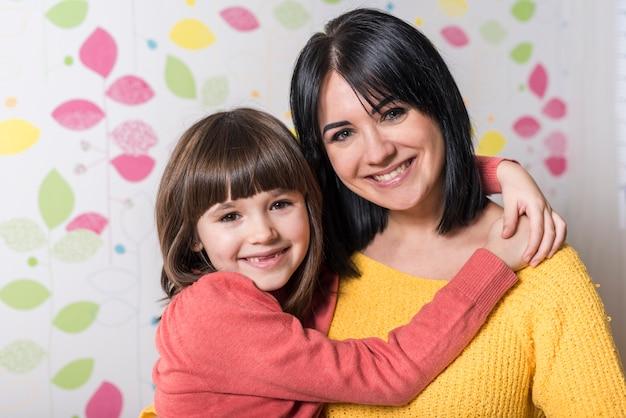 Linda garota abraçando mãe feliz Foto gratuita