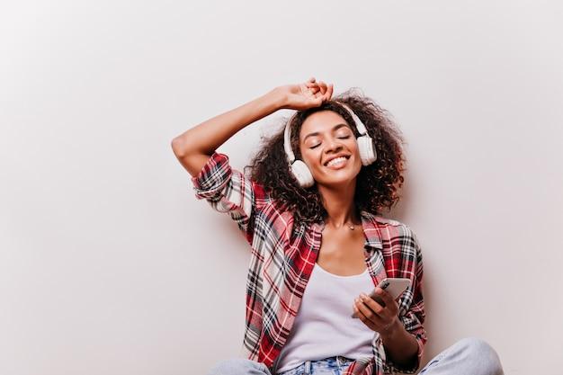Linda garota africana segurando o smartphone e ouvindo música. fascinante modelo feminino curtindo a música com os olhos fechados. Foto gratuita