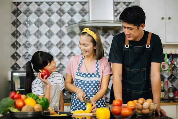 Linda garota ajudar seus pais estão cortando legumes e sorrindo ao cozinhar juntos na cozinha Foto gratuita