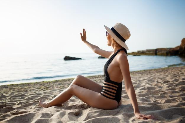 Linda garota alegre vestindo óculos e chapéu baseia-se na praia de manhã Foto gratuita