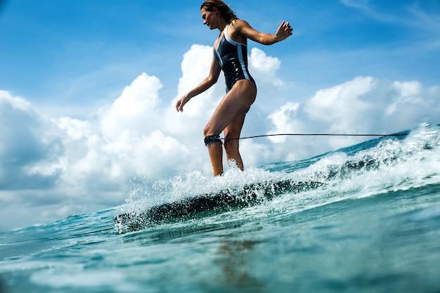 Linda garota andando em uma prancha de surf nas ondas Foto gratuita