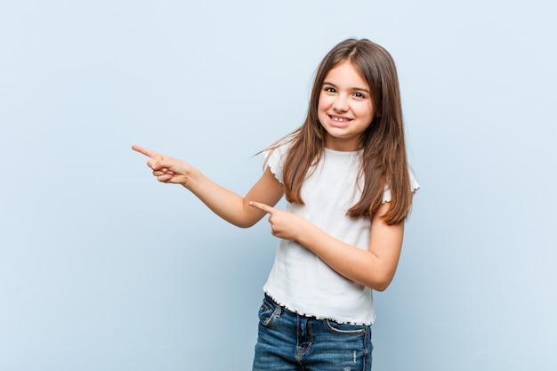 Linda garota animado apontando com o dedo indicador fora. Foto Premium