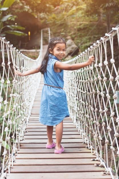 Linda garota asiática criança andando na ponte de corda pendurada do outro lado do rio na floresta Foto Premium