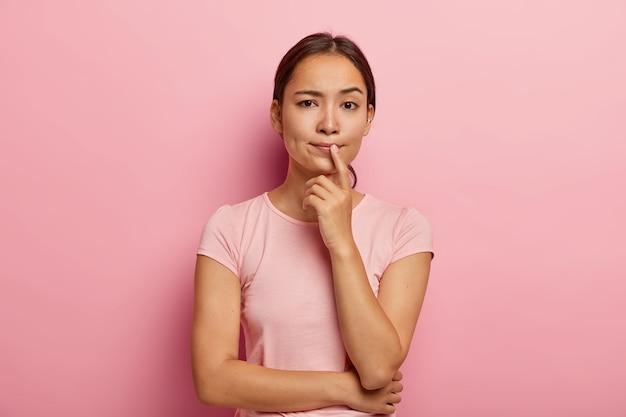 Linda garota asiática pensativa pensa em algo, toma decisões, pondera sobre ações futuras, vestida com roupa casual, tem aparência específica Foto gratuita