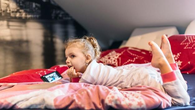 Linda garota assistindo vídeo na cama Foto gratuita