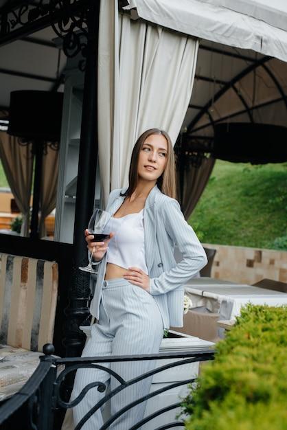 Linda garota bebe vinho na varanda de uma casa bonita. feriado. Foto Premium