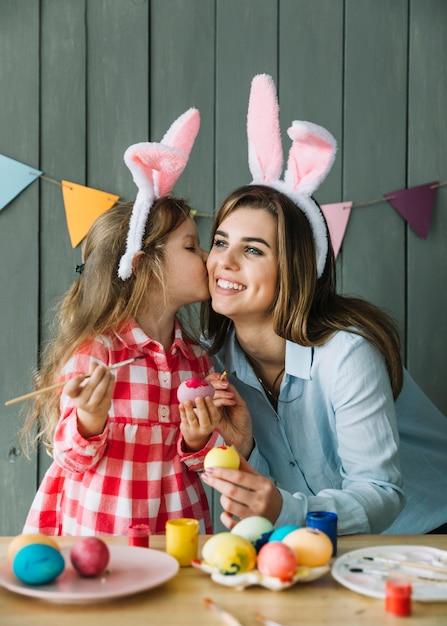 Linda garota beijando a mãe na bochecha enquanto pintava ovos para a páscoa Foto gratuita