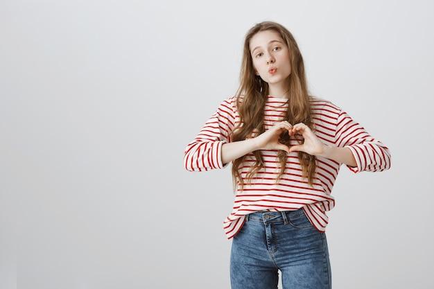 Linda garota boba mostrando gesto de coração, mostrando amor e carinho Foto gratuita