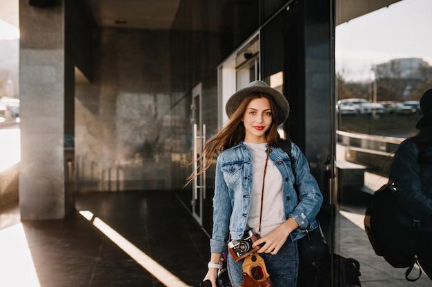 Linda garota bonita com chapéu com expressão de rosto adorável posando do lado de fora enquanto o vento brincando com seu cabelo antes de fazer compras. Foto gratuita