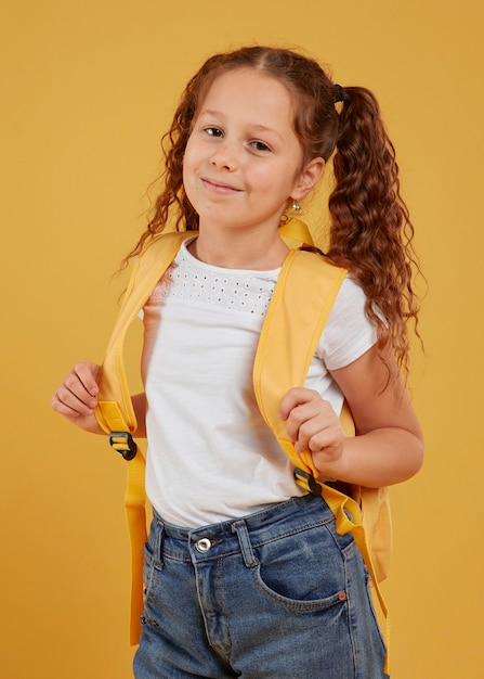 Linda garota carregando mochila amarela Foto gratuita