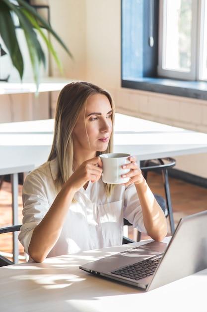 Linda garota caucasiana bebe café e trabalha em um laptop remotamente em um espaço brilhante com plantas verdes. Foto Premium