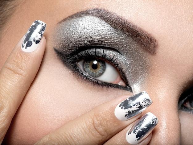 Linda garota com a maquiagem prateada de olhos e unhas de metal. Foto gratuita