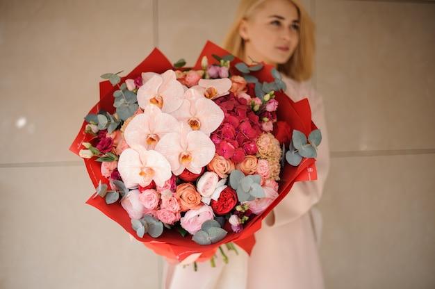Linda garota com buquê de rosas e íris Foto Premium