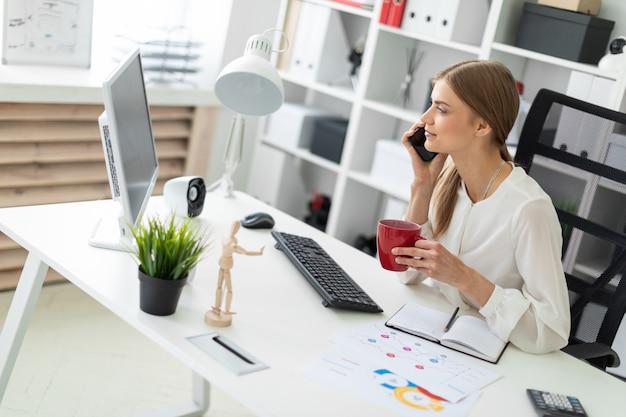 Linda garota com cabelo loiro. uma garota de blusa branca está trabalhando no escritório Foto Premium