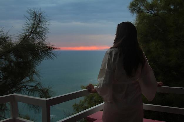 Linda garota com cabelos longos, de pé em um casaco branco na varanda do hotel com vista para o mar e o pôr do sol Foto Premium