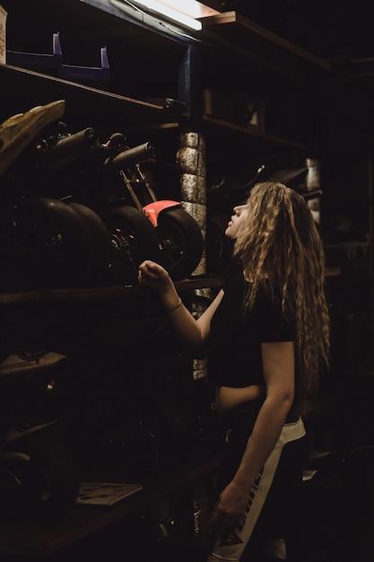 Linda garota com cabelos longos na garagem consertando uma moto Foto gratuita