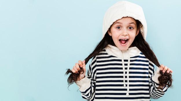 Linda garota com capuz brincando com cabelo Foto gratuita