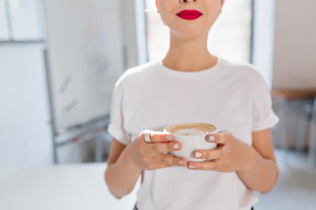 Linda garota com lábios vermelhos e manicure da moda segurando uma xícara de café saboroso, apreciando o sabor em um dia agitado Foto gratuita