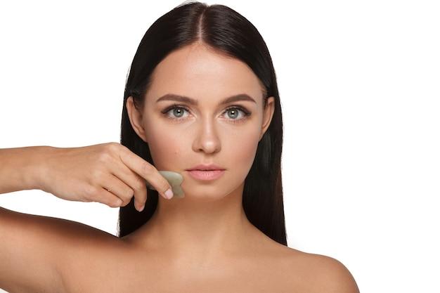 Linda garota com maquiagem natural e pele limpa. segura na mão um limpador de rosto de jade para emagrecer rugas anti-envelhecimento Foto Premium