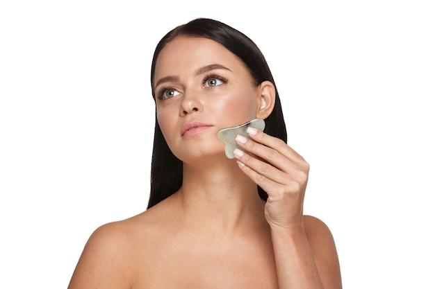 Linda garota com maquiagem natural e pele limpa. segura na mão um limpador de rosto de jade Foto Premium