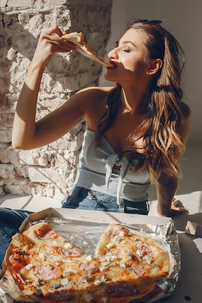 Linda garota com pizza Foto gratuita