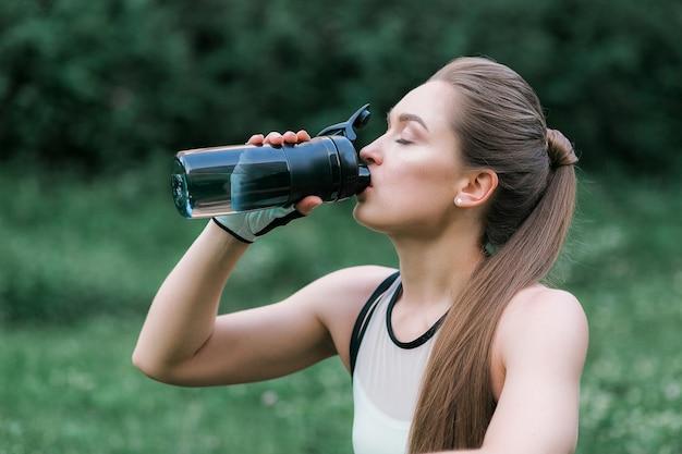 Linda garota com roupas esporte, beber água depois de treino enquanto está sentado na grama Foto gratuita