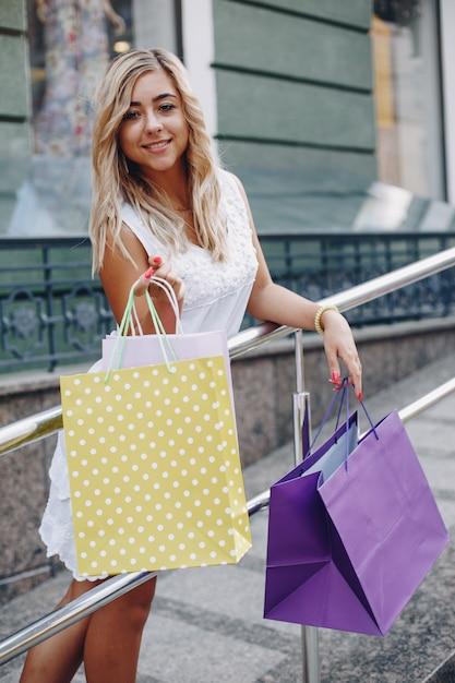 Linda garota com sacola de compras em uma cidade Foto gratuita