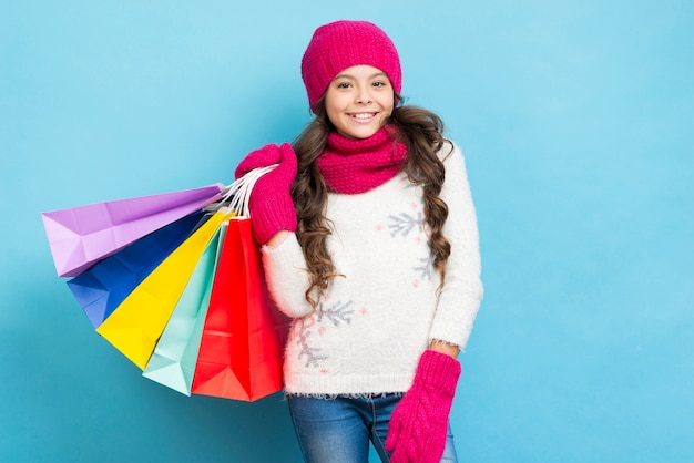 Linda garota com sacolas de compras no ombro Foto gratuita