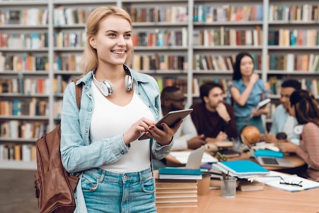 Linda garota com tablet na biblioteca. Foto Premium