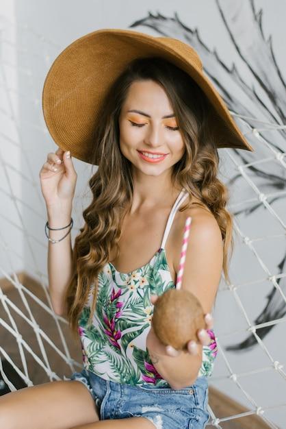 Linda garota com um chapéu de palha de férias, descansando e segurando um coco com um canudo Foto Premium