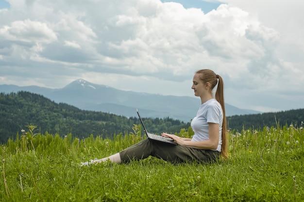Linda garota com um laptop sentado na grama verde Foto Premium