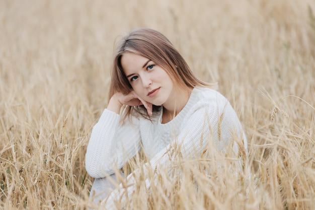 Linda garota com um suéter branco senta-se em um campo de trigo. Foto Premium