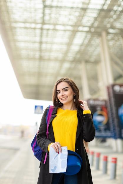 Linda garota com uma mochila atrás do ombro, segurando um mapa, na rua perto do aeroporto Foto Premium