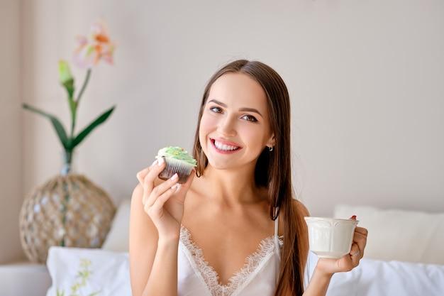 Linda garota comendo bolo e tomando chá na cama Foto Premium