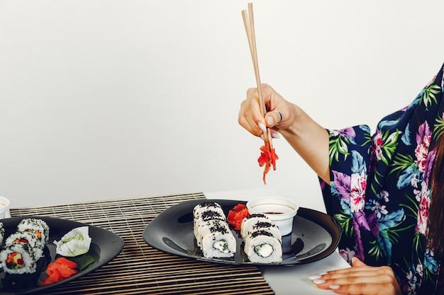 Linda garota comendo um sushi em um estúdio Foto gratuita