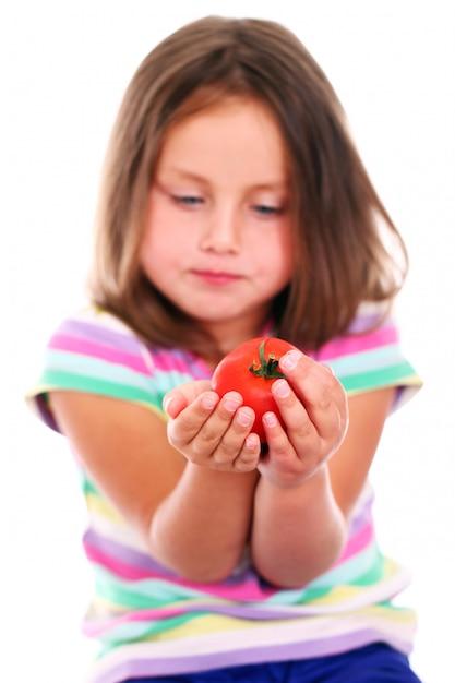 Linda garota comendo um tomate Foto gratuita