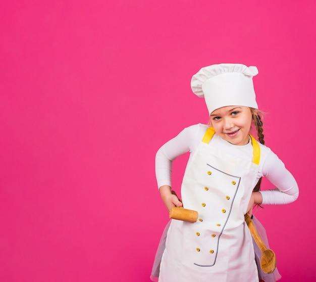 Linda garota cozinhar em pé com utensílios de cozinha Foto gratuita